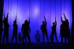 Black silhouettes of people with ropes in their hands at the theater, Shadow play. Human figures on the background of the mysterious stone figures Royalty Free Stock Photos