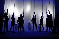 Black silhouettes of people with ropes in their hands at the theater, Shadow play. Human figures on the background of the mysterious stone figures Stock Photo