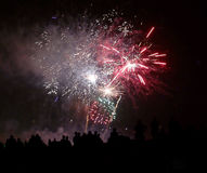 Black silhouettes of people watching the show of fireworks. On the beach Stock Photography
