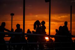 Black silhouettes of people on the waterfront in the orange light of sunset. stock image