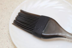 Black silicone pastry brush on white plate Stock Photography