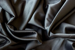 Black silk background. Black abstract background luxury cloth or liquid wave or wavy folds, silk or satin material with waving lines Royalty Free Stock Photos