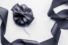 Black silk ribbon and bow on marble background, flatlay. Holiday gift, decoration and sale promotion concept - Black silk ribbon and bow on marble background royalty free stock images