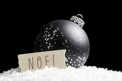 Black and silver ornament sparkling in light, sitting on snow be. Hind simple wooden Noel sign. Christmas and holidays concept Royalty Free Stock Images
