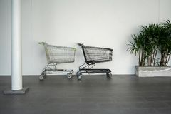 Black and silver shopping carts against the white wall in mall. Black and silver shopping carts against the white wall in shopping mall Royalty Free Stock Images