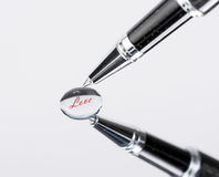 Black, silvery ballpoint pen writing on water drop reflection. Royalty Free Stock Images