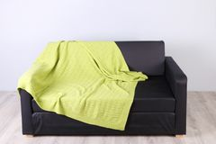 Black simple couch with green plaid. In empty cozy living room Royalty Free Stock Image