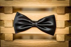 Black simple isolated bow tie. On a wood object Stock Photography