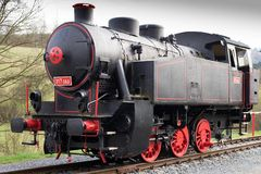 Black single steam locomotive with red wheels. Renovated engine Stock Photos