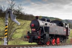 Black single steam locomotive with red wheels. Water pump filling Stock Photography