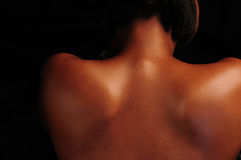 Black Skin II. A black / African-American woman's neck, shoulders and shoulder blades with brilliant copper & mahogany tones Stock Images