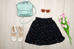 Black skirt, glasses, white shoes, handbag and a bouquet of tulips. Fashionable concept. Wooden background Stock Photography