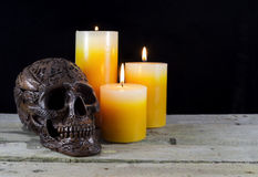 Black skull with candles. Halloween still life with black skull and three candles in the darkness royalty free stock photos
