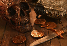 Black skull, coins and dagger in candle light. Black human skull with ancient coins and small sword on old planks in candle light. Pirate and Halloween theme Stock Images