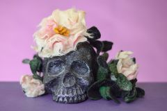 Black skull with flowers and leaves made of wool. Black skull with flowers and leaves on top and around it. Violet background stock image