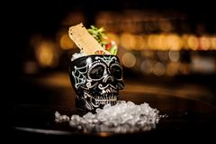 Black skull-shaped glass filled with fresh and sweet summer cocktail. Among ice on the table stock photos