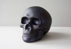 Black skull on white. Black plastic human skull on white background royalty free stock photos