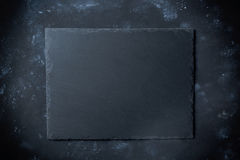 Black slate plate on stone background with top view.  stock photography