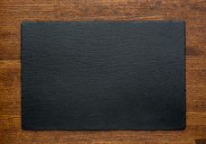 Black slate stone on wooden background, top view Stock Photo