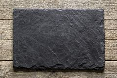 Black slate texture closeup. Black slate board on grunge wooden table closeup. Natural texture. Can be used like food background royalty free stock photography