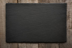 Black slate tile on wooden background. Top view. Image with copy space Royalty Free Stock Images