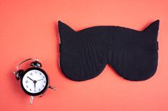 Black sleep mask with clock on pink background composition, cat mask with ears. Flat lay and top view photo, sleeping, bed, rest, relax, relaxation, people stock image