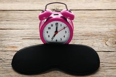 Black sleeping mask with alarm clock. On grey wooden table Royalty Free Stock Photo