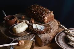 Black sliced bread on the board, butter and honey, flax seed, than slicing bread on the table and a wooden background on a stump, stock image