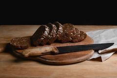 Black sliced bread on the board, vintage knife on the table and the old background, concept of healthy eating, place for text, set stock photo