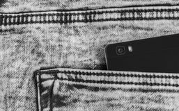 Black smart phone covered with water drops in jeans pocket. Smart phone camera isolated on jeans texture Royalty Free Stock Photography