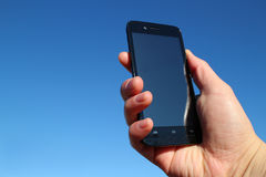 Black smart phone and the hand in the blue sky #2 Stock Photography