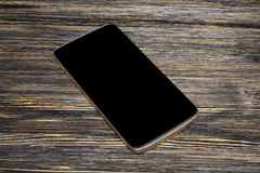 Black smart phone with isolated screen on old wooden desk Stock Image