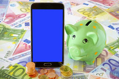Black Smart phone and Piggy Bank. Black smart phone with blue blank touchscreen and a green Piggy Bank on a background of Euro banknotes and coins Royalty Free Stock Photos