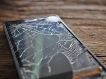 Black smartphone broken glass on old wooden board in the concept of mobile maintenance, accidental damage. In the insurance royalty free stock images