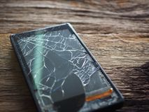 Black smartphone broken glass on old wooden board in the concept of mobile maintenance, accidental damage. In the insurance stock photo