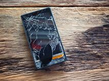 Black smartphone broken glass on old wooden board in the concept of mobile maintenance, accidental damage. In the insurance royalty free stock photo