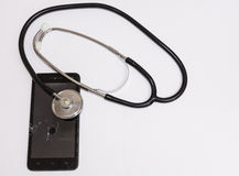 Black smartphone with broken glass and stethoscope. Royalty Free Stock Photos