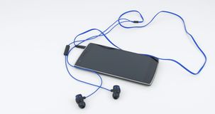 Black smartphone with connected sports earphones. Slow panning movement over black smartphone with connected sports earphones on white background stock video footage