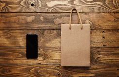 Black smartphone and craft paper bag on wooden table. Mockup of a black smarthpone lying next to a craft paper bag with light brown string handles on a beautiful Royalty Free Stock Image