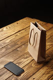 Black smartphone and craft paper bag on wooden table royalty free stock images