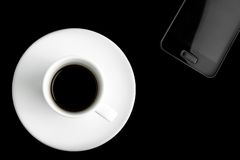 Black smartphone and cup of coffee Stock Photo