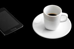 Black smartphone and cup of coffee Stock Image