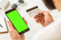 A black smartphone with green screen for chroma key Online payments plastic card compositing Hand holding black. Black smartphone with green screen for chroma Stock Photography