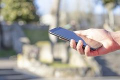 Black smartphone in hand in the park in the open air, lit by the sun royalty free stock photos