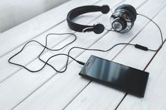 Black smartphone and headphones on a desk Stock Photos