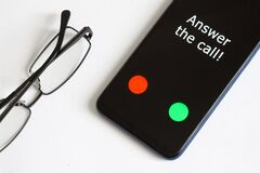 Black smartphone with an incoming call and the inscription: Answer the call lies on a white background next to the glasses.