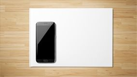 Black smartphone white paper on wooden background stock photography