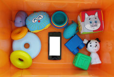 Black smartphone with white screen among the toys Stock Photo