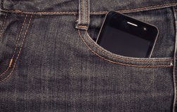 Black smartphone in your pocket jeans. background. Stock Image
