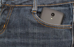 Black smartphone in your pocket jeans. background. Royalty Free Stock Photo